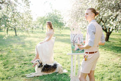 Artist with watercolor painting of bride in wedding dress outdoo Stock Image