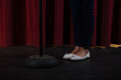 Artist in white shoes standing behind closed curtain Stock Photo