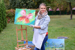 Artist woman holds painting and looks at it, posing at camera an Stock Images