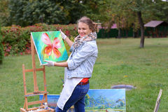 Artist woman holds painting and looks at it, posing at camera an Royalty Free Stock Photo