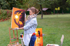 Artist woman holds painting and looks at it, posing at camera an Stock Photos