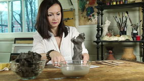 Artist woman sculpts from a clay in a studio stock video