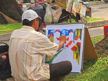 Artist at work. An artist painting a colorful piece of work Royalty Free Stock Photo