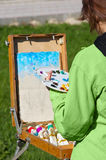 Artist at work. Young female artist working at open air, creating oil paint. selective focus Stock Image