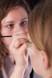 An artist making the flower tattoo on the face of. An artist making the flower on face of her model royalty free stock images