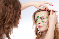 An artist making the flower tattoo on the face of. Her model royalty free stock images