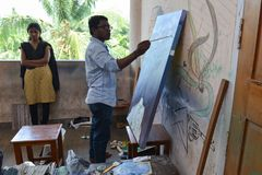 Artist at work in messy place College, India. Ernakulam, India - January 19, 2016: RLV College of Music and fine arts. Male student painting his picture on the stock photos