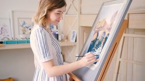 Artist painting watercolor canvas easel channel. Artist at work. Watercolor paper canvas on easel. Young lady making brushstrokes painting water. Fall. Bridge stock video footage
