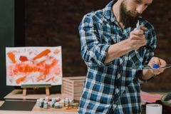 Artist man artwork paints palette creative idea. Artist at work. Young bearded man, paints on palette. Serious facial expression. Focus on creative idea. Artwork royalty free stock image