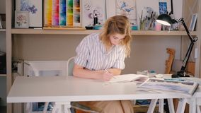 Artist work sketching drawing project creativity. Artist at work. Young blonde woman sitting at desk sketching drawing. Project in process. Inspiration stock video footage
