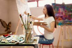 Artist Working On Painting In Studio. Background image, selective focus on foreground Royalty Free Stock Photos