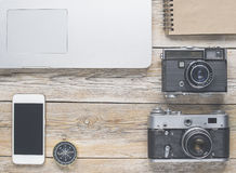 Artist working place. With notebook, smartphone and vintage cameras Royalty Free Stock Image