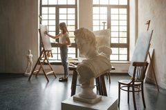 Artist at the working process. Young woman creating the painting. Workshop room with light and classical sculpture busts royalty free stock photography