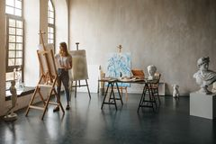 Artist at the working process. Young woman creating the painting. Workshop room with light and classical sculpture busts royalty free stock image