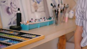 Artist workplace studio woman hand paint box. Artist workplace. Neatly organized home art studio. Woman hand taking paint box palette closeup. Watercolor stock footage