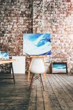 Artist workplace. Painting on canvas on the easel in the studio. Different paintbrushes and paints on wooden table. Concept. Verti. Cal. Art loft space Stock Photo