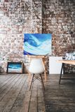 Artist workplace. Painting on canvas on the easel in the studio. Different paintbrushes and paints on wooden table. Concept. Verti. Cal. Art loft space Royalty Free Stock Photo
