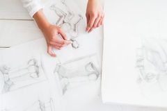 Artist workplace with pencil pictures flat lay. Top view on table with different sketches and female artist hands, drawing female silhouette. Art, craft Royalty Free Stock Images