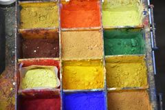 Colorful color powder pigments  at a workplace of an artist. Artist workplace with various colorful powder pigments in bright colors Royalty Free Stock Photography