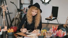 Artist works on drawing. Female artist working on drawing, colouring the portrait of a man with black pencil, enjoying the process at desk packed with number of stock video footage