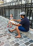 Artist works on portrait of small girl by the iron fence of Sacre Coeur, Paris, France Royalty Free Stock Images