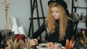 Artist works on sketch. Focused artist working on sketch, drawing the picture with black pencil, typical day of professional painter in art studio stock video