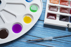 Artist workspace composition with brush, palette and watercolor on a blue wooden background. Royalty Free Stock Image