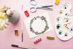 Artist workspace. Floral wreath frame hand painted with watercolor, bouquet of chrysanthemum and roses, glasses, paintbrush, sciss Stock Photo