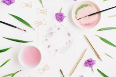 Artist workspace. Floral wreath frame painted with watercolor, paintbrushes, golden pen and clips, green leaves. Flat lay, top view Royalty Free Stock Photography