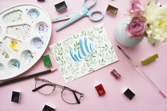Artist workspace. Hello written in calligraphy style, palette, watercolor, brush, glasses, scissors, bouquet of flowers on a pink Stock Photography