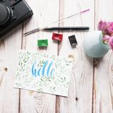 Artist workspace. `Hello` written in calligraphy style, palette, watercolor, brush, vintage photo camera, bouquet of roses. Artist workspace. Hello written in Stock Photo