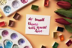Artist workspace. Inspiration quote. Do small things with great love written in calligraphy style, red tulips, watercolor, palettes on a peach background. Flat Royalty Free Stock Image