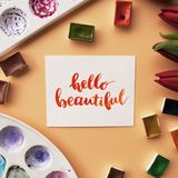 Artist workspace. Inspirational quote. Hello beautiful written in calligraphy style, red tulips, watercolor, palettes on a peach background. Flat lay Royalty Free Stock Photography