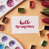 Artist workspace. Inspirational quote. Hello gorgeous written in calligraphy style, red tulips, watercolor, palettes on a peach background. Flat lay Royalty Free Stock Photo