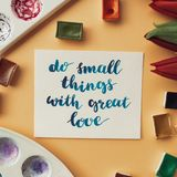 Artist workspace. Inspirational quote do small things with great love written in calligraphy style, red tulips, watercolor. Artist workspace. Inspirational Royalty Free Stock Image