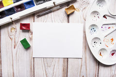 Artist workspace with watercolor, brush, palette, white paper on a wooden background. Royalty Free Stock Photos