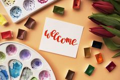 Artist workspace. Word welcome written in calligraphy style, red tulips, watercolor, palettes on a peach background. Flat lay. Royalty Free Stock Photos
