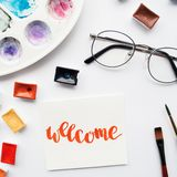 Artist workspace. Word Welcome written in calligraphy style, watercolor cuvettes and palette on a white background. Artist workspace. Word Welcome written in Royalty Free Stock Photo
