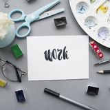 Artist workspace. Word work written in calligraphy style, glasses, paintbrush, scissors, watercolor, palette on a gray background. Flat lay Stock Photos