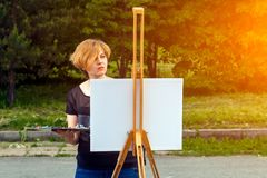 A close-up artist paints. Artist young woman paints on a canvas an urban landscape of a summer of oil paints in city park royalty free stock photos