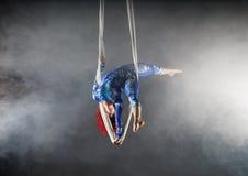Artista aéreo atlético do circo com o ruivo no traje azul que está em uma mão na seda aérea foto de stock