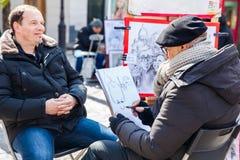 Artista barbudo mayor que trabaja en el Place famoso du Tertre en Montmartre fotos de archivo libres de regalías