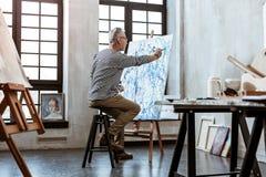 Artista barbuto di talento che si siede sulla sedia e che dipinge sulla tela fotografia stock