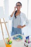Artista bonito alegre que tiene una llamada de teléfono Imagen de archivo libre de regalías