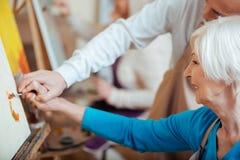 Artista che aiuta il suo collega anziano nella classe della pittura fotografia stock