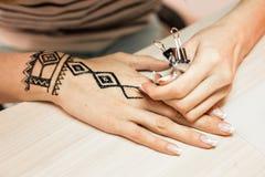 Artista che applica il tatuaggio del hennè sulle mani delle donne Mehndi è arte decorativa indiana tradizionale Primo piano Immagine Stock
