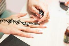 Artista che applica il tatuaggio del hennè sulle mani delle donne Mehndi è arte decorativa indiana tradizionale Primo piano Fotografie Stock