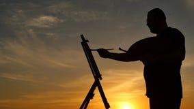 Artista che dipinge una siluetta dell'immagine al movimento lento panoramico del colpo di tramonto stock footage