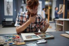 Artista che pensa sulla sua pittura Immagine Stock