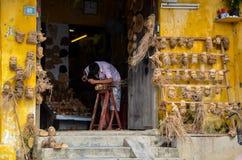 Artista che scolpisce le teste umane fatte delle radici di legno immagine stock libera da diritti
